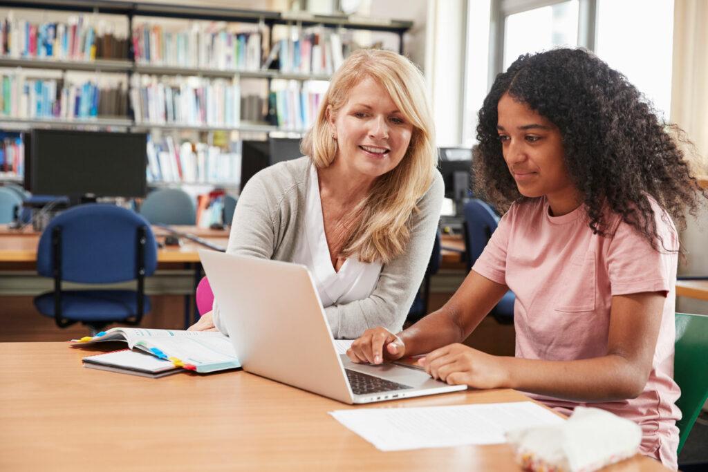 Eine Lehrerin arbeitet mit einer Schülerin am Laptop